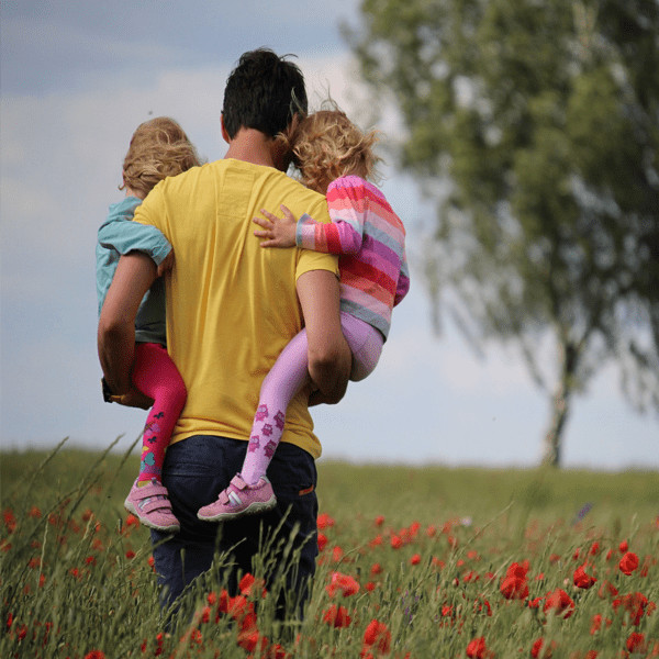 Photograph of a father holding 2 kids in a field of flowers